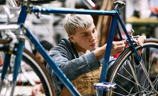 Young female mechanic repairing bicycle brake at workshop. Confident employee is working at repair shop. She is wearing apron.