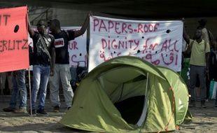 """Des migrants réclament """"des papiers, un toit et la dignité pour tous"""", le 5 août 2015 sur le quai d'Austerlitz à Paris"""