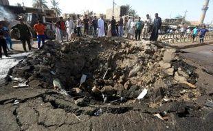 Photo prise le 18 juillet 2015 du cratère formé par l'explosion d'une voiture piégée revendiquée par l'EI dans la ville à majorité chiite de Khan Bani Saad au nord de Bagdad