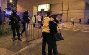 Des spectateurs du concert d'Ariana Grande sous le choc après le probable attentat qui a frappé une salle de concert de Manchester, le 22 mai 2017.