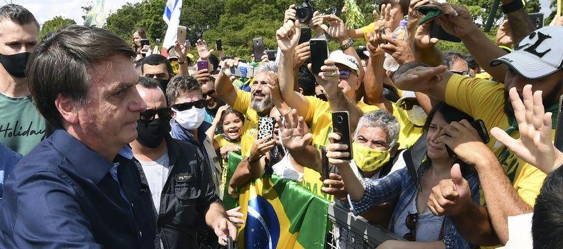 Le président brésilien Jair Bolsonaro salue les partisans à son arrivée au Palais Planalto à Brasilia, le 24 mai 2020, au milieu de la pandémie de coronavirus COVID-19.