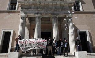 """Des militants """"antiautoritaires"""" déploient une bannière après avoir réalisé un brève incursion au Parlement grec à Athènes, le 1er avril 2015, en solidarité avec des prisonniers en grève de la faim"""