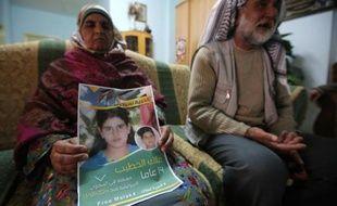 Ali al-Khatib et sa femme Khaoula montrent le 27 janvier 2015 près du village de Biline, en Cisjordanie, une affiche réclamant la libération de leur fille Malak, de 14 ans, la plus jeune prisonnière palestinienne détenue en Israël
