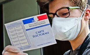 Illustration. Un jeune homme tenant une carte d'électeur en main.