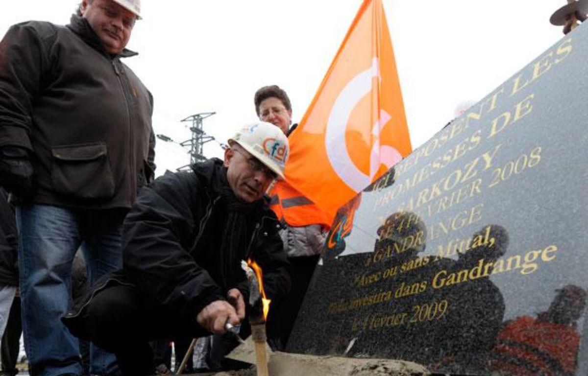 Des ouvriers d'Arcelor-Mittal ont posé une stèle un an après les promesses de Nicolas Sarkozy que celui-ci n'a pas tenu.  – JEAN-CHRISTOPHE VERHAEGEN/AFP