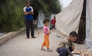 Illustration d'un homme et des enfants dans un camp de réfugiés de Lattaquié, à Syrie, le 23 octobre 2015.