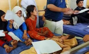 Des enfants attendent d'être examinés après des rumeurs de réactions à un vaccin anti-polio, le 22 avril 2019 au Pakistan.