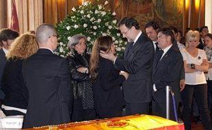 Le Premier ministre espagnol Mariano Rajoy (au centre droit) tient dans ses bras, le 13 mai 2014, la fille de la dirigeante locale du parti conservateur assassinée la veille à Leon