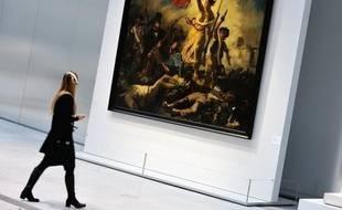 """La femme qui a vandalisé le tableau de Delacroix """"La liberté guidant le peuple"""", joyau du Louvre-Lens, a écrit """"AE911"""" au feutre indélébile noir, mais l'inscription semblait pouvoir être nettoyée, ont indiqué à l'AFP des sources concordantes."""