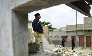 Un policier pakistanais devant une maison détruite appartenant à des talibans à Karachi, le 21 août 2015