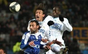 Les Marseillais Heinze (au centre en blanc) et Diawara à la lutte avec l'Auxerrois Hengbart, lors d'un match de L1 au Stade Vélodrome, le 23 décembre 2009.