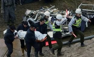 Des militaires emportent le corps d'une victime du crash aérien le 6 juin 2015 à Tapei