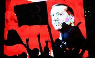 Des partisans d'Erdogan devant un écran diffusant son portrait lors d'un rassemblement à Ankara le 20 juillet 2016