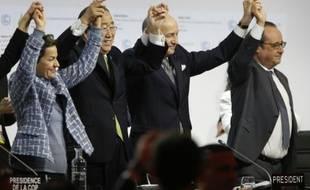 Laurent Fabius (c), Ban Ki Moon et François Hollande (d) à l'annonce de l'adoption de l'accord sur le climat au Bourget, le 12 décembre 2015