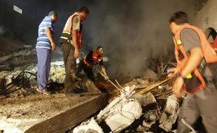 Des Palestiniens dans les ruines d'une maison détruite par un tir israélien le 19 août 2014 à Gasa