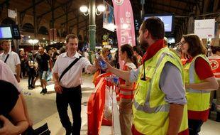 Des membres de la Croix Rouge distribuent de l'eau aux voyageurs coincés dans la soirée à la Gare du Nord, le 19 juillet 2016 à Paris