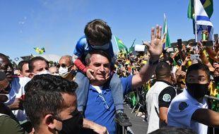 Jair Bolsonaro porte le fils d'un de ses partisans sur ses épaules lors d'un rassemblement à Brasilia, le 31 mai 2020.