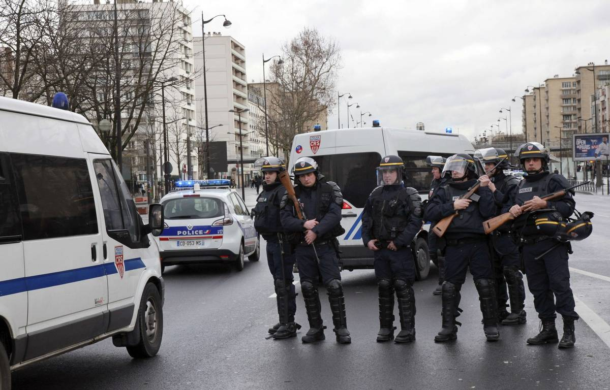 French police officers arrive to take up positions near Porte de Vincennes in Paris on January 9, 2015, after at least one person was injured when a gunman opened fire at a kosher grocery store and took at least five people hostage, sources told AFP. The attacker was suspected of being the same gunman who killed a policewoman in a shooting in Montrouge in southern Paris on January 8. AFP PHOTO / LOIC VENANCE – AFP
