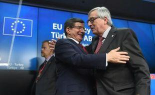 Le Premier ministre turque Ahmet Davutoglu (g), salue le président de la Commission européenne Jean-Claude Juncker, lors d'une conférence de presse à la fin d'un sommet entre l'Union européenne et la Turquie, à Bruxelles, le 29 novembre 2015