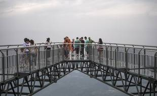 Une passerelle au plancher en verre emmène les touristes à plus de 120 mètres au-dessus du vide, au bord d'une falaise du sud-ouest de la Chine.