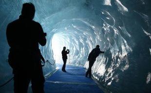 """Des touristes visitent la """"Grotte de glace"""" le 8 juin 2015 sur le glacier surnommé la """"Mer de Glace"""", à Chamonix-Mont-Blanc, dans les Alpes françaises"""