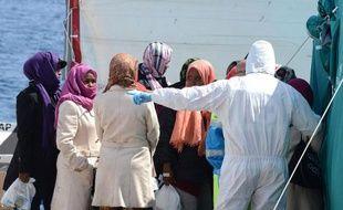 La Croix Rouge italienne aide des migrants à leur arrivée à Messine en Sicile le 15 avril 2015