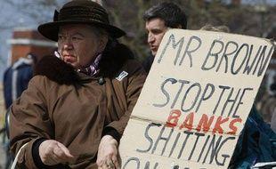 Une femme tient une pancarte alors qu'elle manifeste à Londres aux abords de la réunion du G20, le 2 avril.