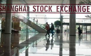 """This photo taken on October 16, 2014 shows people shows people walking inside the Shanghai Stock Exchange building in Shanghai. When the Shanghai and Hong Kong stock exchanges """"connect"""" on November 17 it will open multi-billion-dollar channels for investors to play both markets, but some Chinese punters say it looks more like a bad trade. AFP PHOTO / JOHANNES EISELE"""
