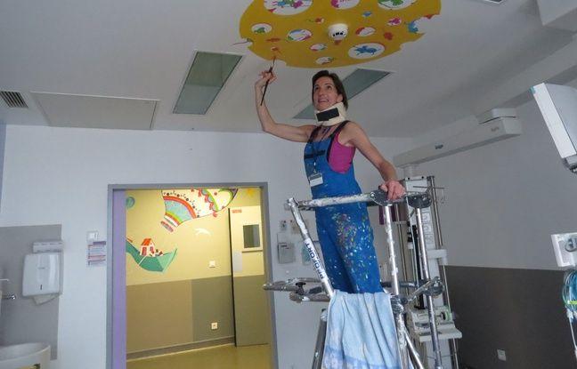 Edith Baudoin, artiste et clown à l'hôpital, peint avec une minerve pour éviter d'avoir mal à la nuque les plafonds des chambres du service de réanimation pédiatrique de l'hôpital Necker (AP-HP), à Paris.