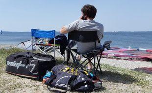 Un concurrent des championnats du monde de windsurf glande sur la plage, en attendant que le vent se lève.