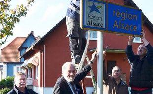 Le maire et des conseillers municipaux démontent le panneau région Alsace, pour le nettoyer