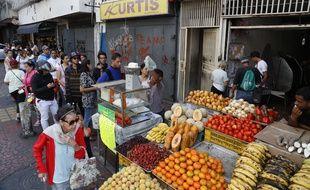 Des Vénézuéliens font la queue pour acheter à manger, malgré la coupure d'électricité qui les empêche d'utiliser leur carte bancaire.