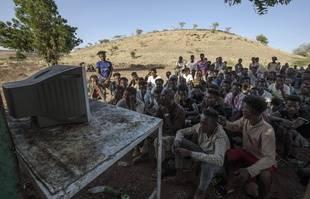 Des réfugiés qui ont fui le conflit dans la région éthiopienne du Tigray, regardent les informations sur une télévision, au camp de réfugiés d'Umm Rakouba à Qadarif, dans l'est du Soudan, le samedi 5 décembre 2020.