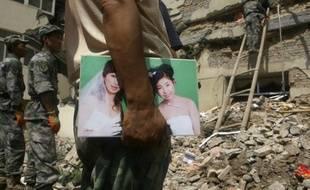 Un homme attend des nouvelles de sa femme, disparue dans des glissements de terrain dans la région de Gansu, en Chine, le 9 juillet 2010.