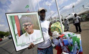 Un homme vend le 28 mai 2015 dans les rues d'Abuja une photo encadrée de Mohammadu Buhari et des drapeaux de son parti