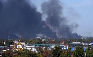 Des colonnes de fumée s'élèvent près de l'aéroport de Donetsk soumis aux tirs d'artillerie de l'armée ukrainienne et des rebelles prorusses, le 14 septembre 2014