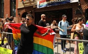 Une femme pose devant le Stonewall inn, à New York, lieu des mythiques émeutes entre communauté LGBT et policiers, en juin 1969.