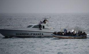 Des gardes-côtes italiens escorte un bateau à bord duquel se trouve des migrants, en direction de l'île italienne de Lampedusa le 14 mars 2011