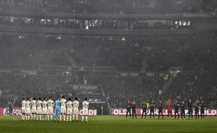 Les joueurs lyonnais et parisiens respectent ici la minute d'applaudissements dédiée à Paul Bocuse, dimanche avant OL-PSG à Décines. JEFF PACHOUD