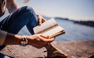 Une jeune femme lit un roman.