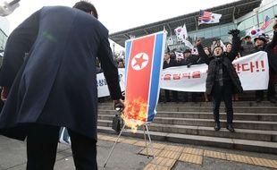 Des Coréens du Sud brûlent un drapeau de la Corée du Nord pour protester contre le rapprochement entre les deux nations à l'occasion des JO d'hiver 2018.