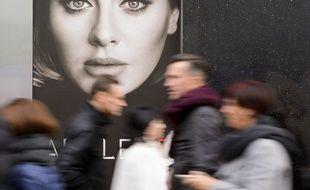 Des passants marchent devant une affiche publicitaire d'Adele, à Londres, en novembre 2015. Jonathan Hordle/REX Shutterstock