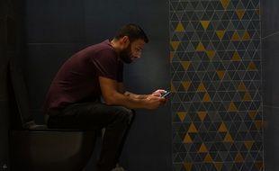 Un homme aux toilettes avec son portable.