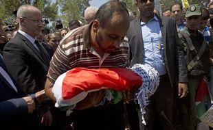 Un membre de la famille tient le corps du bébé Palestinien de 18 mois tué dans un incendie criminel, pendant son enterrement le 31 juillet 2015 dans le village de Duma, en Cisjordanie.