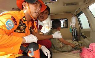 Des secouristes indonésiens prennent en charge un survivant après le naufrage d'un ferry sur l'île de Sulawesi le 20 décembre 2015