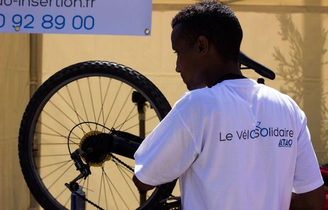 Un salarié de l'association est en train de réparer un vélo.