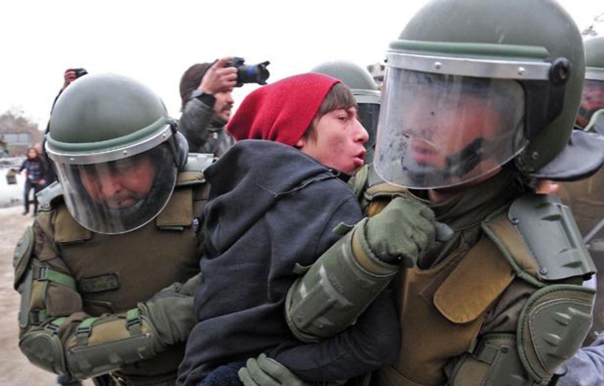 Un étudiant arrêté par des policiers lors de manifestations à Santiago du Chili, le 4 août 2011. – C.SANTANA / AFP