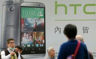 Des gens passent devant la publicité du dernier smartphone de HTC, le 6 janvier 2015 à Taipei