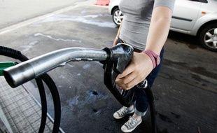 Une femme tient un pistolet à essence dans une station service. Illustration station service.