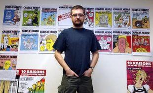 """Le dessinateur Charb pose devant les Unes de Charlie Hebdo, dont il était le directeur, le 27 décembre 2012, le jour où il présentait à la presse un album intitulé """"La Vie de Mahomet"""""""